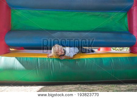 Portrait of happy boy playing on bouncy castle at playground