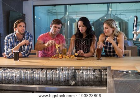Friends having food and drink while standing at bar counter