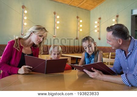 Family reading menu while sitting at table in restaurant