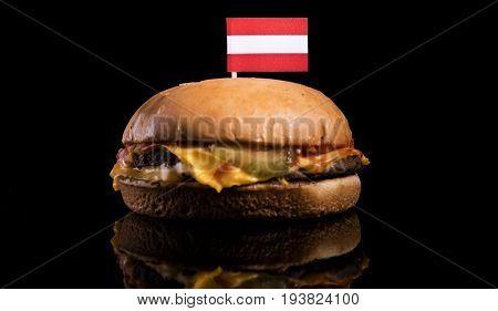 Austrian Flag On Top Of Hamburger Isolated On Black Background