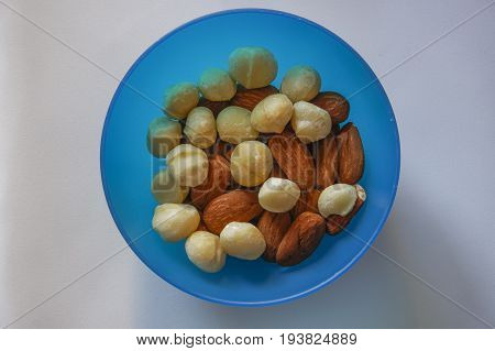 Macadamia and almonds mixed roasted nuts top closeup view. Collection of healthy nuts served on a blue plastic bowl.