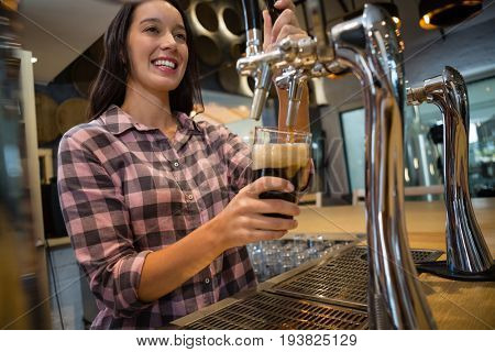 Beautiful smiling barmaid preparing drink at restaurant