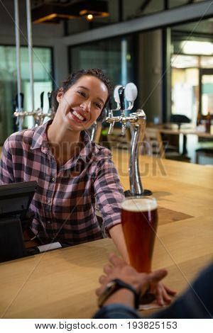 Happy barmaid serving drink to male customer at bar counter