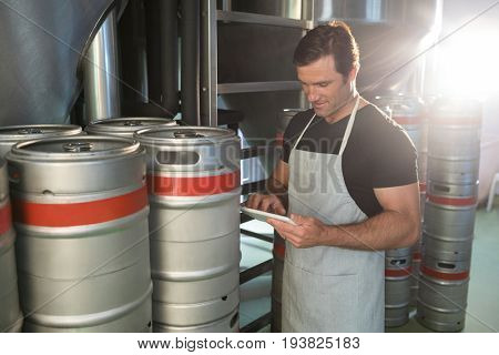 Worker using digital tablet while standing by kegs at warehouse