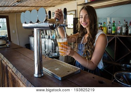 Portrait of young barmaid pouring beer from tap in glass while standing at bar