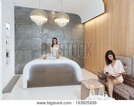 Receptionist and guest at elegant beauty salon.