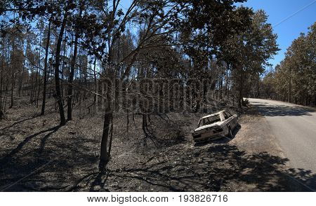 Road through the burnt forest and a car also completely burnt bye the side of the road. Pedrogao Grande Portugal.