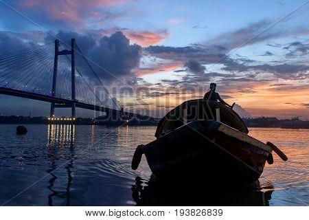 June 29,2017, Kolkata , West Bengal,India. Silhouette of Vidyasagar Setu bridge at twilight with a wooden boat on Hoogly river.,