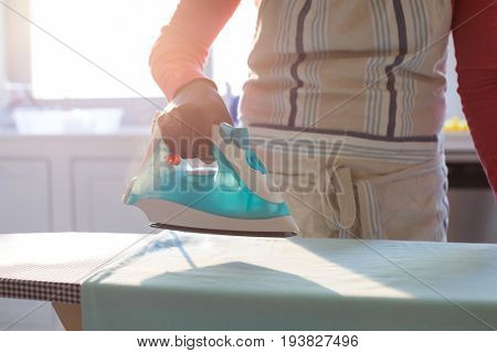 Mid section of woman ironing shirt on ironing board in kitchen at home