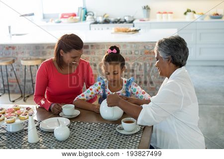 Happy multi-generation family having tea in dining table at home
