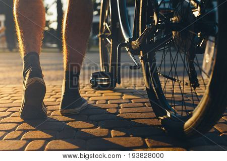 Closeup Of Male Feet And City Bicycle Wheels Rear View And Low Angle Holiday Weekend Activity