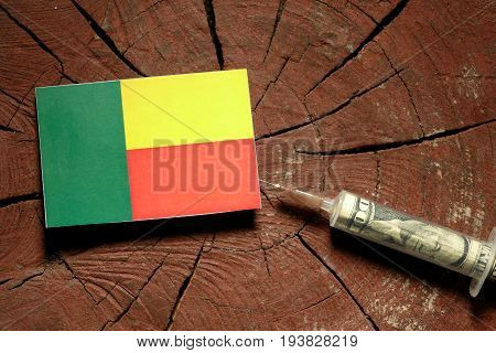 Benin Flag On A Stump With Syringe Injecting Money In Flag