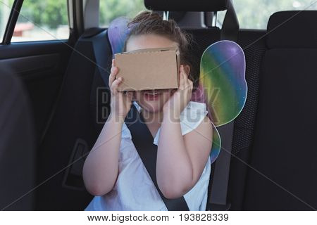 Girl pretending to use virtual reality headset in car