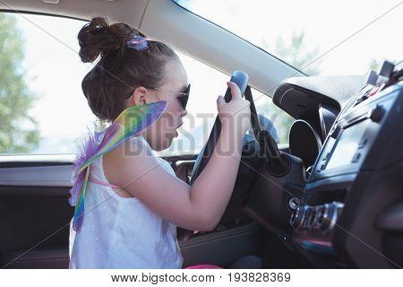 Cute girl pretending to drive a car