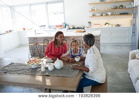 Portrait of happy multi-generation family having tea in dining table at home