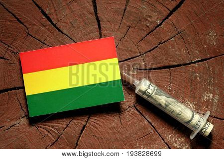 Bolivian Flag On A Stump With Syringe Injecting Money In Flag