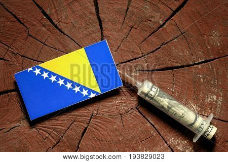 Bosnia And Herzegovina Flag On A Stump With Syringe Injecting Money In Flag