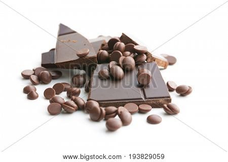 Tasty chocolate morsels and chocolate bar isolated on white background.