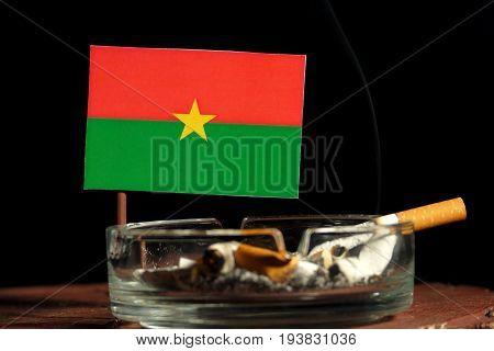 Burkina Faso Flag With Burning Cigarette In Ashtray Isolated On Black Background