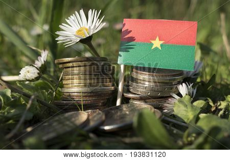 Burkina Faso Flag With Stack Of Money Coins With Grass And Flowers