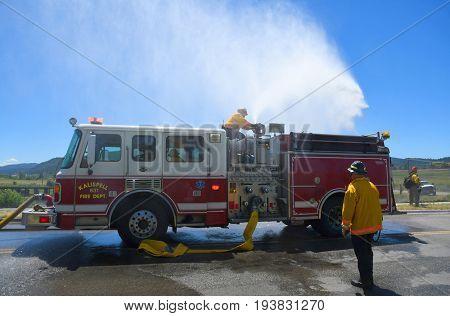 KALISPELL, MONTANA, USA - June 21, 2017: Firefighter sprays water onto a grass fire from the top of a fire truck