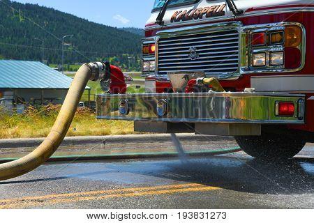 KALISPELL, MONTANA, USA - June 21, 2017: Fire truck pumps water into a hose at scene of a grass fire