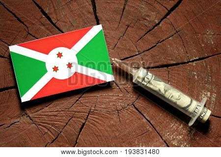 Burundi Flag On A Stump With Syringe Injecting Money In Flag