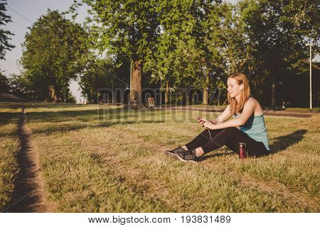 Relaxing Outdoor. Young Woman Sitting In The Park, Relaxing After Running And Using Her Smartphone.