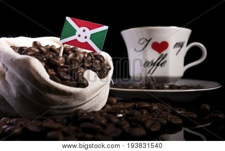 Burundi Flag In A Bag With Coffee Beans Isolated On Black Background