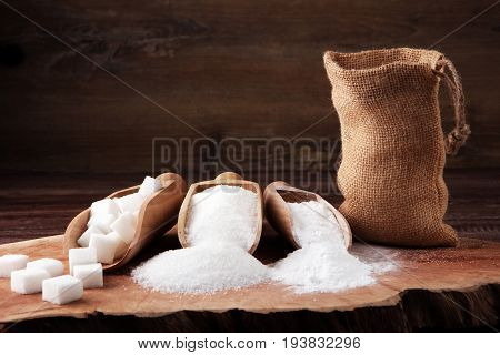 Scoop With White Sand And Lump Sugar On Brown Wooden Background
