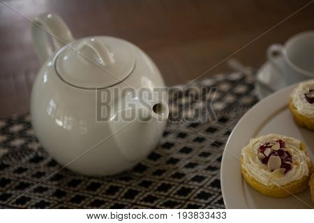 Close-up of teapot and dessert on place mat