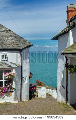 A narrow picturesque street in the small and beautiful village of Clovelly. Between the white houses you can see the sea and the distant shore of Wales. A popular tourist destination in the UK. Devon. England