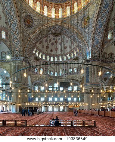 Istanbul Turkey - April 16 2017: Interior of Sultan Ahmed Mosque (Blue Mosque) with a huge pillars arches colored stained glass windows and tourists visiting the mosque Istanbul Turkey