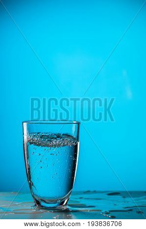 Glass of water on blue background, studio photo