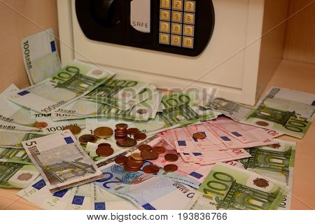 Money and coins lie in front of locked safe