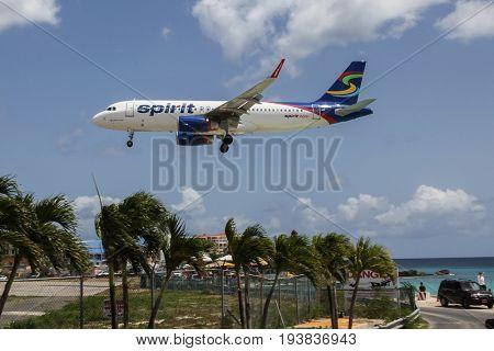 ST. MAARTEN-AUGUST 1: Aeroplane Airbus A320 Spirit is landing on Princess Juliana International Airport, over Maho Bay Beach seen in St.Martin/St.Maarten on August 1, 2015