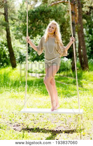 Beautiful blonde woman swinging on the rope swing at the background of summer forest