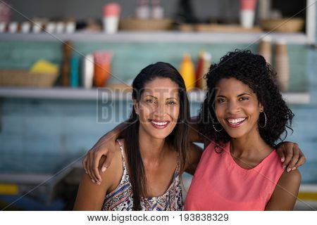 Portrait of smiling friends sitting with arm around