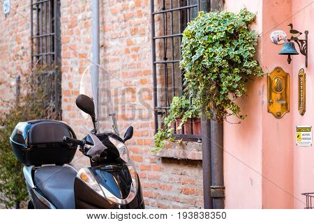 Ferrara, Italy - June, 30, 2017: Motorcycle parked near the entrance of an inhabited house in a center of Ferrara, Italy
