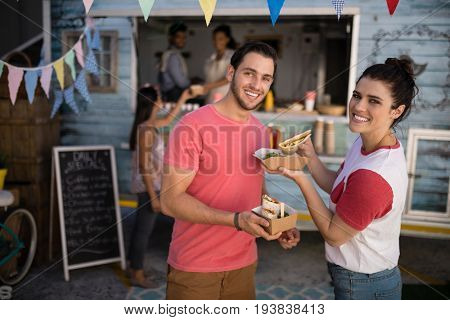 Portrait of smiling couple standing with snacks