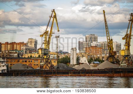 Loading and unloading of sand by crane. The shore of the river Moscow