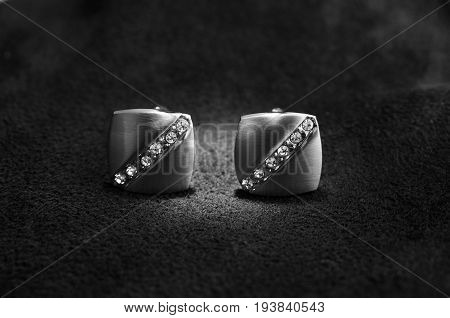 Silver cufflinks with rhinestone on the black matter at the center of the cufflinks catches the light