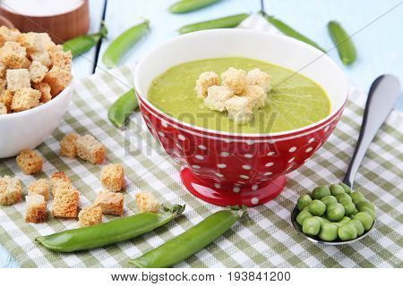 Green Peas Soup In Bowl With Rusks On Wooden Table