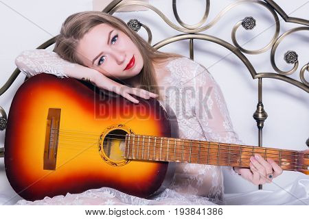 beautiful young woman playing music on a bed with happiness and guitar.