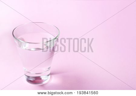 Glass with water on the pink background