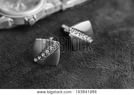 Silver cufflinks with rhinestone on the black matter near the watches black and white photo