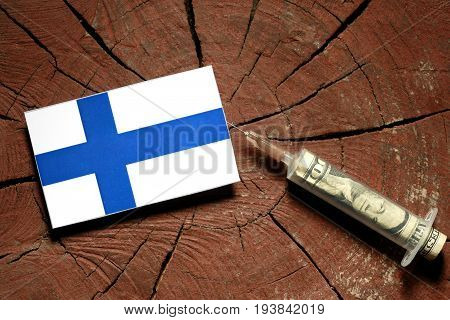 Finnish Flag On A Stump With Syringe Injecting Money In Flag