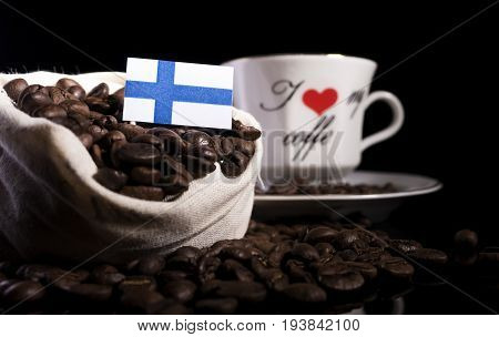 Finnish Flag In A Bag With Coffee Beans Isolated On Black Background