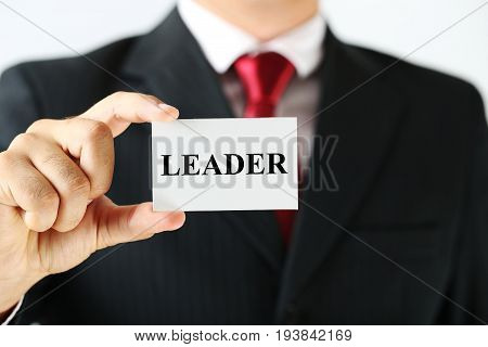 Businessman holding card with the word Leader