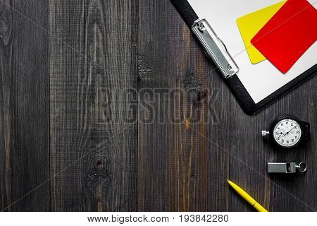 Yellow and red referee cards and whistle on wooden background top view.